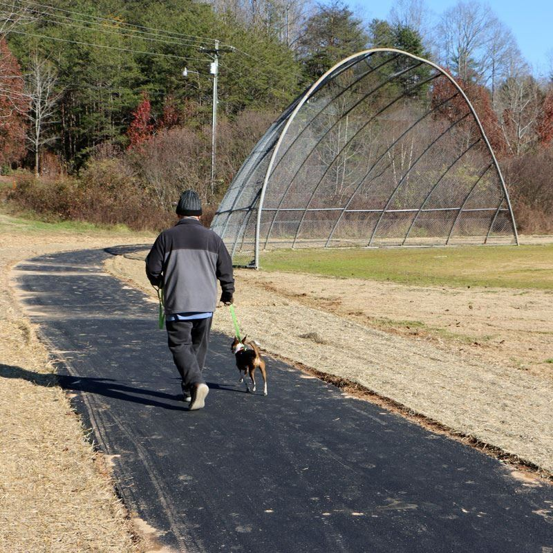 A man walks a dog on the new greenway at Wilson Park.