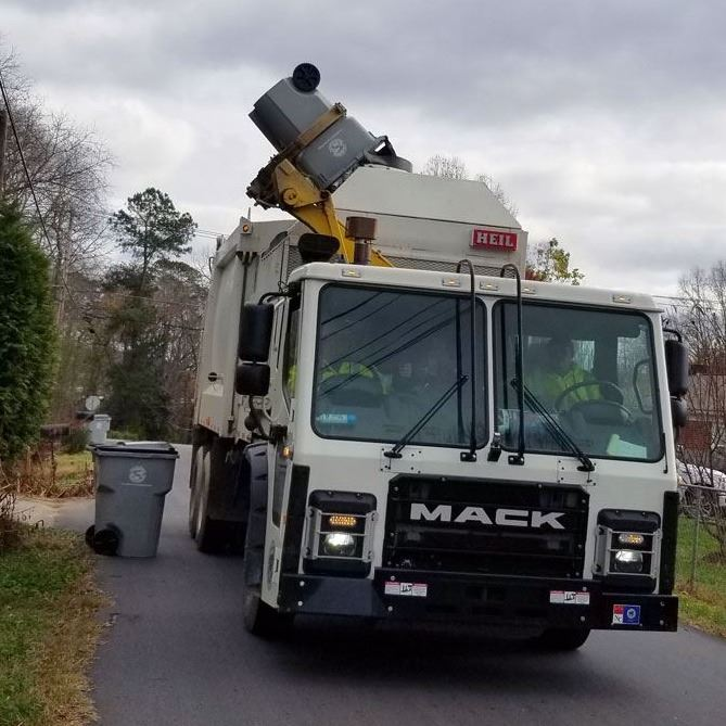 An automated garbage truck collects empties a City of Lenoir garbage cart