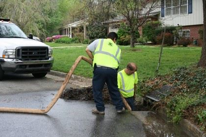 Two men working in street drain